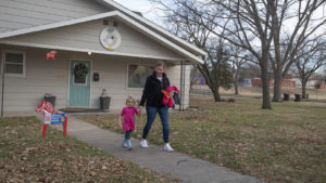 picture of mother leading young daughter out the door to child care facility for the day